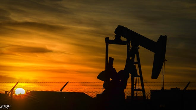 The silhouette of a pump jack looms over a rising sun.