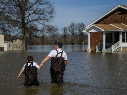 Gabriel Skaggs, 7, and Rev. Barry Skaggs wade through flood water between their home (left) and Beals Pentecostal Church (right), where Barry is a pastor, in Reed, Kentucky, Tuesday, Feb. 27, 2018. After Barry gave him a pair of waders, Gabriel spent time playing in the water around his home on Tuesday afternoon. Gabriel hasn't missed any school days due to flooding because he is home-schooled.