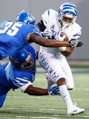Memphis running back Timothy Taylor (right) is brought down by defenders Tim Hart (left) and 'Bryan Goodson (middle) during their spring football game at Liberty Bowl Memorial Stadium.