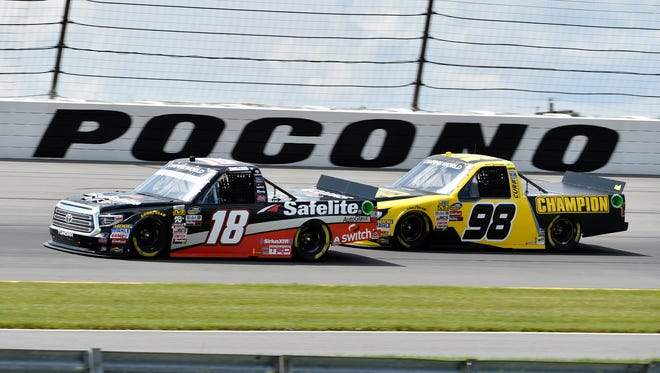Erik Jones (18) drives past Grant Enfinger (98) in Turn 3 on Saturday. Jones, a Michigan native, made his first start in the Truck Series in two years.