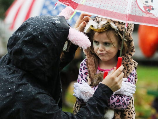 Paige Jackson and daughter, Annie, 5, try to stay dry prior to walking in the annual Fairmount neighborhood Halloween Parade Saturday, Oct. 31, 2015, in Salem, Ore.