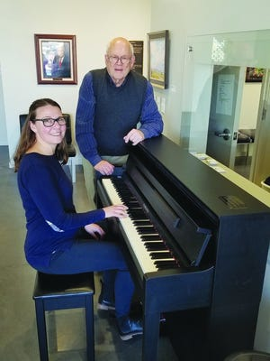 Vernon Filley Art Museum co-directors Brittany Novotny (seated) and Stan Reimer (standing) enjoy the multi-functions of a special clavinova piano, purchased for the museum from funds donated in memory of Dr. James Van Blaricum.