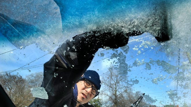 Nashville resident Steve Harych scrapes ice off his windshield before temperatures drop below zero later tonight  onTuesday Feb. 17, 2015, in Nashville in Tenn.