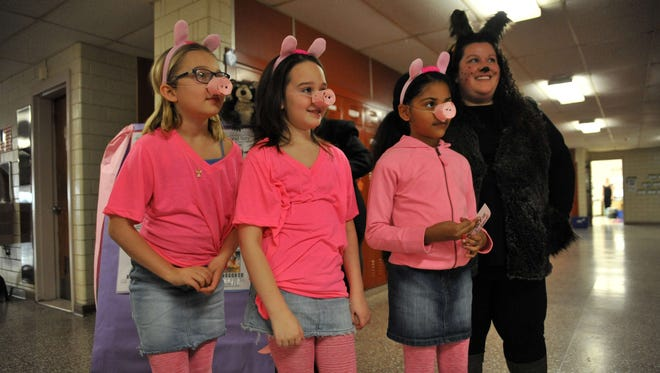 Third-graders Gabby Chopek (from left), Clare Twomey and Nina Watts, all 9, dressed as three little pigs, with their teacher Ashley Bartholomew dressed as the wolf during Rieck Avenue Elementary's Adventures in Learning event Wednesday.