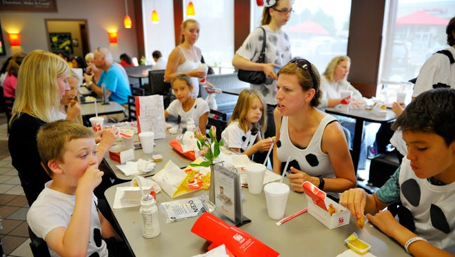 Customers dressed as cows eat chicken at Chick-fil-A in Woodbridge, Va., on National Cow Appreciation Day Tuesday, July 12.