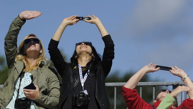 Molly McHugh, left, and Emiko Shinozaki watch the Antares rocket climb through the sky at Wallops Island on Wednesday.  Staff photo by Jay Diem Molly McHugh (left) and Emiko Shinozaki watch the Antares rocket climb through the sky at Wallops Island on Sept. 18, 2013. The rocket carried the Cygnus spacecraft to the International Space Station on a demonstration resupply mission.