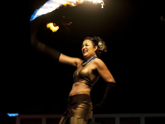 Member of the fire performance group Obsidian Butterfly, Stacey Smith, performs on Saturday, July 26, 2014 in downtown Reno, Nev., during the Reno Compression event.