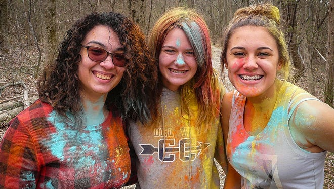 Diversity Club President Destiny Bonilla (left) and potential participants Samantha Ruby (center) and Trinity Mikuta experiment with the festive coloration that will adorn the runners in the April 28 Rainbow Fun(d) Run.