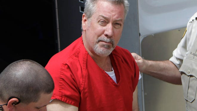FILE - In this May 8, 2009 file photo, former Bolingbrook, Ill., police officer Drew Peterson arrives for court in Joliet, Ill. Peterson, convicted of killing his third wife and suspected in his fourth wife's disappearance, was charged in February with soliciting an unidentified person to find someone he could pay to kill Will County State's Attorney James Glasgow who helped put him in prison. (AP Photo/M. Spencer Green, File)