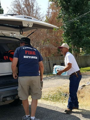 Members of the Retired Farmington Firefighters group help deliver bottled water to Harvest Gold residents on Thursday.