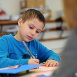 Ameer Aiyash, 7, reads a note, Monday, Mar. 21, during Paws for Success, part of Pathways for Potential, at Woodrow Wilson Elementary.