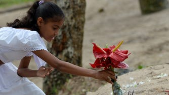 A Sri Lankan girl commemorates the victims of the Dec. 2004 tsunami, offering flowers, prayers and alms during a special ceremony.