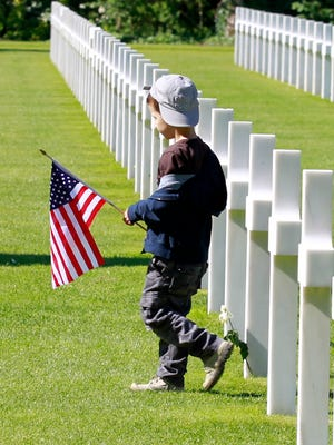 A young visitor carrying the U.S. flag walks among graves at the Colleville American military cemetery, in Colleville sur Mer, western France.