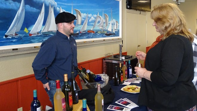 Winery representatives chatted with guests about the various types of wine they were sampling during the wine festival.