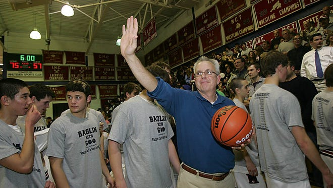 Mendham coach Jim Baglin salutes the fans as he leaves the gym while attaining his 600th career victory in 2009.