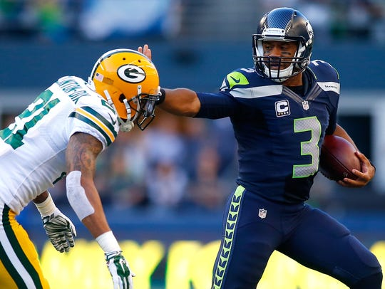 Seahawks quarterback Russell Wilson stiff arms Packers