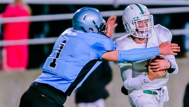 Lansing Catholic's Tony Poljan, left, sacks Gabriel Richard's Jack Gaderick during a Week 8 contest. In addition to being a standout quarterback, Poljan is also a contributor on a Cougar defense that is allowing just 8.2 points per game.