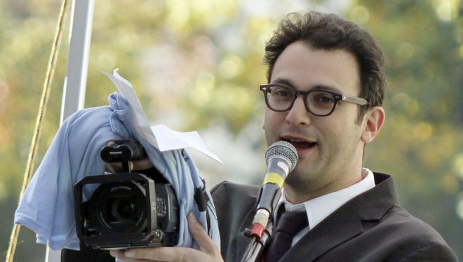 """In this Nov. 3, 2010 file photo, filmmaker Josh Fox, who made """"Gasland"""" an Oscar-nominated documentary film about the dangers of fracking, holds up a video camera as he speaks at a rally of protestors in Pittsburgh."""