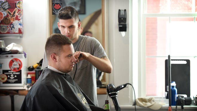 The Black Comb Barbershop at 31 E. Orange Street in Lancaster has just moved around the corner, providing classic services. Barber Evan Demers cuts Ryan Quindlen hair.
