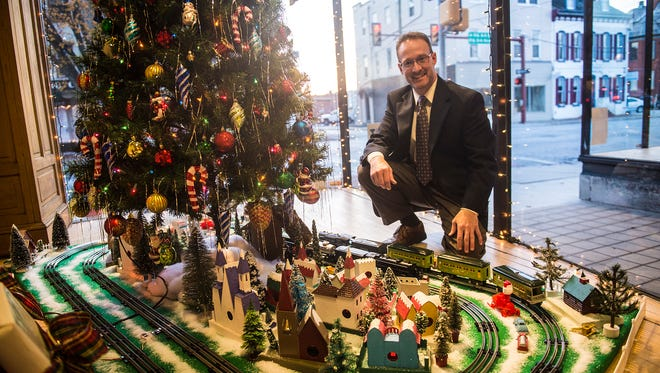 David Dubs, owner of Hanover Clothing, poses for a photo next to the train set that is on display in the store's front window on Dec. 10, 2015. The trains, a 1933 #259E Lionel Passenger set and a 1948 #1655 Lionel Freight set originally belonged to former Hanover resident William Walker.