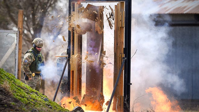 Police officers and sheriff deputies watch as an explosive charge is used to breach a door Sunday, April 10, during classes for the Special Operations Training Association members in St. Cloud.