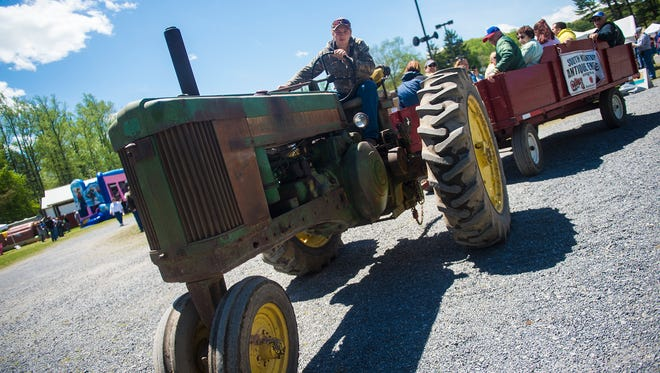 Driver Brandon Bowling, of Biglerville, takes a wagon full of visitors for a hayride on Sunday at the annual Apple Blossom Festival at the South Mountain Fairgrounds.