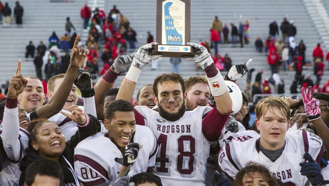 Hodgson's Kyle Taylor holds the championship trophy high after his team defeated Laurel High School 42-0 in the DIAA Division II State Championship football game at Delaware Stadium in Newark on Saturday afternoon.