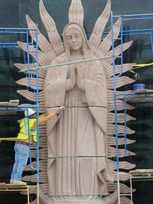 Pablo Hernandez smooths a joint on a 30-foot statue of Our Lady of Guadalupe at a new shrine outside St.Mark's Catholic Church in east El Paso Wednesday.