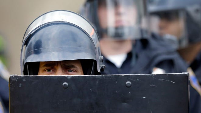 Baltimore police officers monitor protesters on April 27.