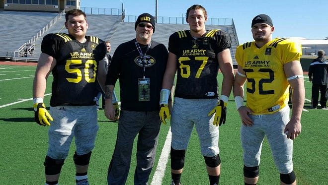Kentucky commitments (left to right) Drake Jackson, Landon Young and Kash Daniel pose with Doss High School coach Phil Hawkins during U.S. Army All-American Bowl practice.
