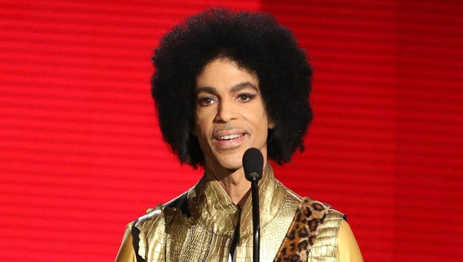 """FILE - In this Nov. 22, 2015 file photo, Prince presents the award for favorite album - soul/R&B at the American Music Awards in Los Angeles. Prince, widely acclaimed as one of the most inventive and influential musicians of his era with hits including """"Little Red Corvette,"""" ''Let's Go Crazy"""" and """"When Doves Cry,"""" was found dead at his home on Thursday, April 21, 2016, in suburban Minneapolis, according to his publicist. He was 57. (Photo by Matt Sayles/Invision/AP, File)"""