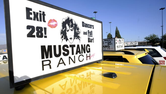 Taxis at the Reno-Tahoe International Airport display ads for the Mustang Ranch brothel.
