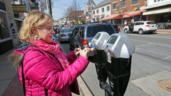 """Wendy Hassiepen, a Newark business owner, uses her credit card to pay a meter on Main Street, Thursday, March 27, 2014. Forty """"smart"""" parking meters are part of a pilot program on Main Street between Haines and Academy streets."""