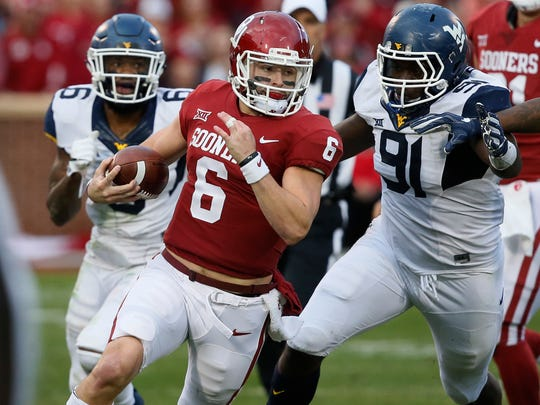 Oklahoma quarterback Baker Mayfield avoids West Virginia defenders during their game in 2017.