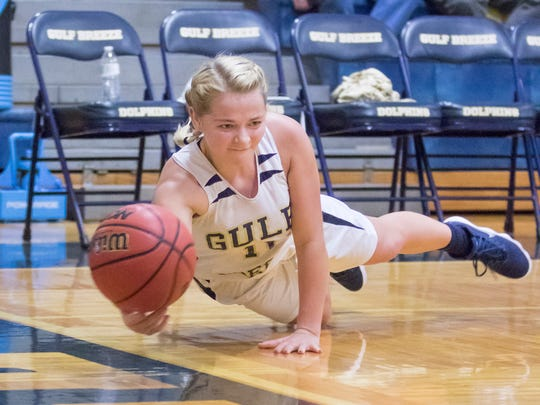 Sadie Nix (11) dives in an attempt to keep the ball inbounds during the Gulf Breeze vs. Letcher County Central (Kentucky) girls basketball game in the Innisfree Hotels Pensacola Beach basketball tournament at Gulf Breeze High School on Thursday, December 28, 2017.