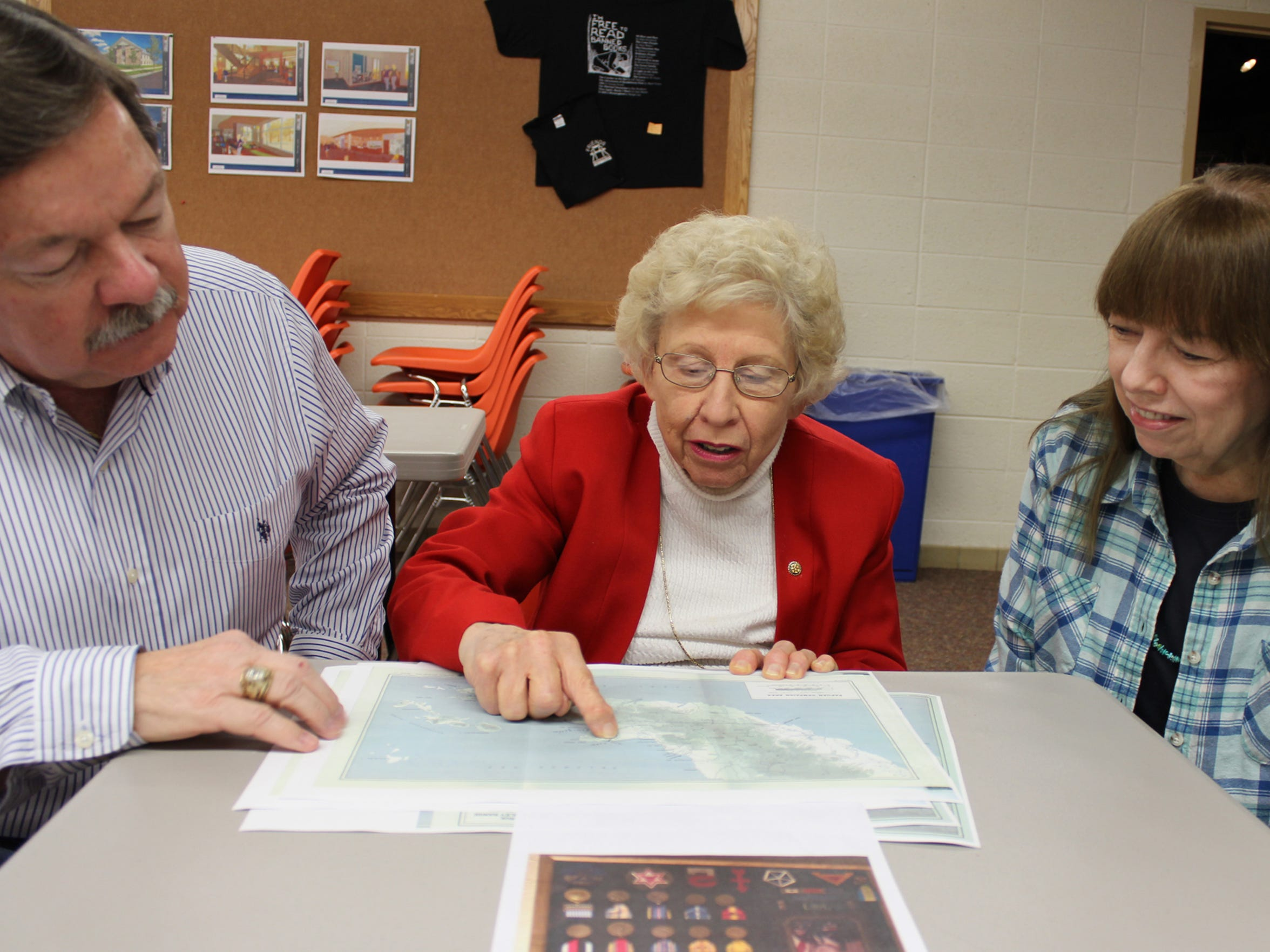 Marshfield Historian Shirley Mook, center, shows Jerry Seidl and Carol Seidl (both of Austin, Texas) where their father was wounded in a battle on the island of Papua during a battle in World War II, in the basement of the Marshfield Public Library Oct. 19.
