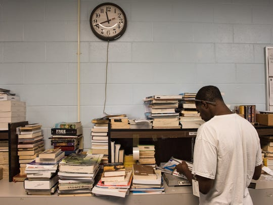 An inmate library worker sorts through stacks of books.