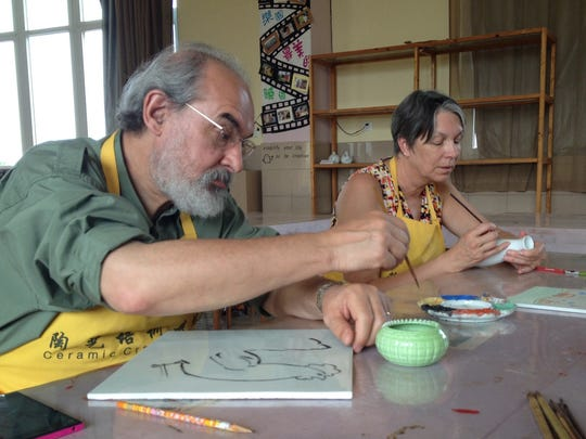 Bob Kohout and Mary Lopas paint on white glaze at the Jingdezhen Teacher's College.