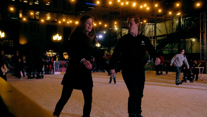 Grace Daly, left, and Rob Lechner, right, ice skate during the 37th Annual Light Up Louisville downtown Friday night on Jefferson Street.  Nov. 24, 2017