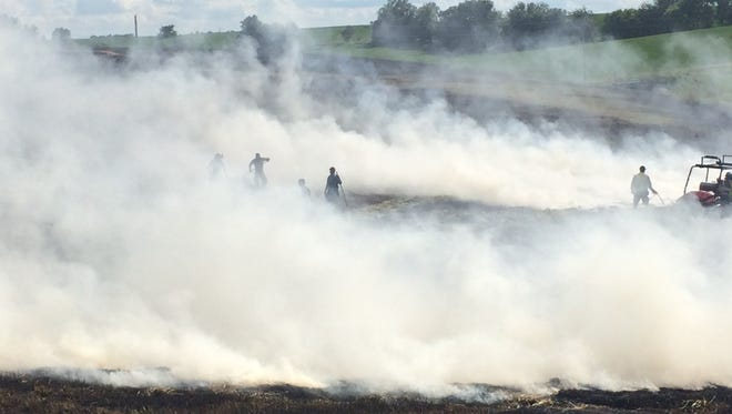 This photo of firefighters with the Grinnell Fire Department and Malcom Volunteer Fire Department surrounded by smoke as they battle a field fire at 60th and Newburg Rd. on Monday, June 26 received the 2nd place award at the 2018 Iowa Newspaper Association convention.
