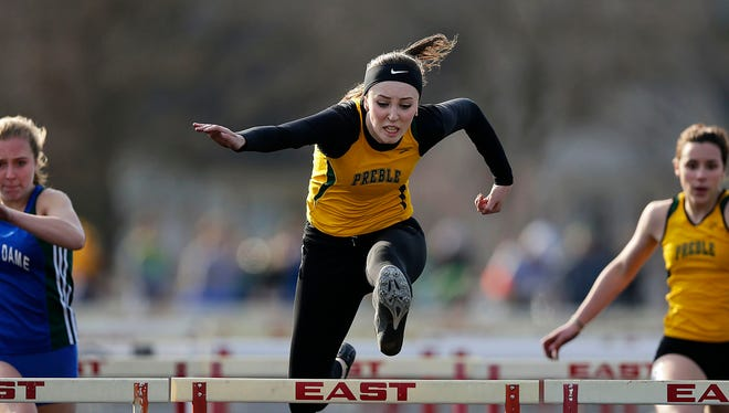In middle, Green Bay Preble's Hayley Winzenried soars over a hurdle while competing in the 100-meter hurdles on  April 14 at Green Bay East High School. Winzenried has the fastest times in both hurdles events this season among local competitors.