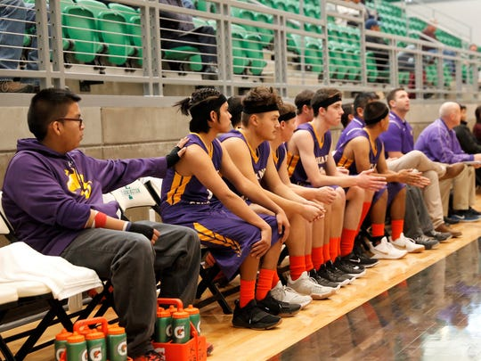 The Kirtland Central boys basketball team wears black headbands and orange socks in support of Aztec High School after Thursday's shooting at AHS.