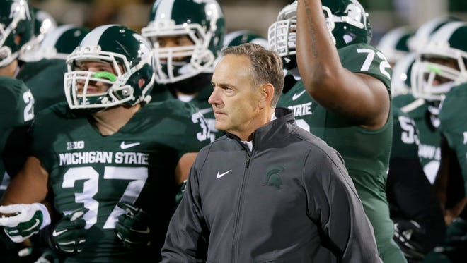 Michigan State head coach Mark Dantonio walks with his team before last week's game against Ohio State. The test this week is partly MSU's resolve.