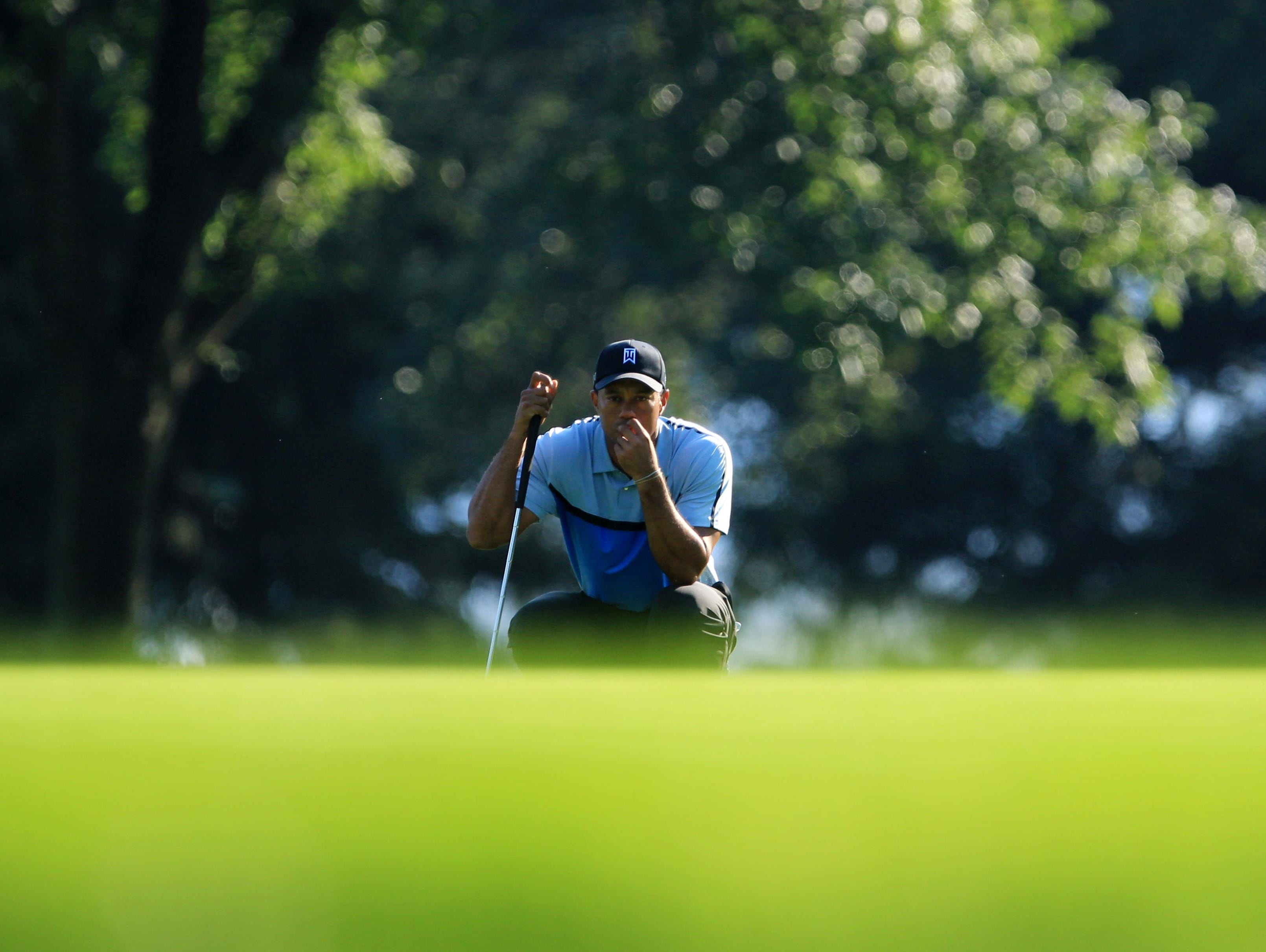 Tiger Woods lines up a putt on the 10th green, his first hole of the tournament.