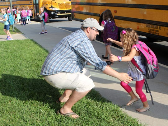 """Savannah Ayton jumps into the arms of her father, Jordan Ayton, on Monday at the  J. Ralph McIlvaine Early Childhood Center in Magnolia, where kindergartners were starting their first day of school. Jordan drove three hours to see this """"milestone moment."""""""