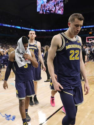 Michigan Wolverines guard Duncan Robinson (22) and guard Zavier Simpson (3) react as they leave the court after losing to the Villanova Wildcats in the championship game of the 2018 men's Final Four at Alamodome.