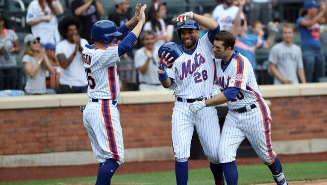New York Mets second baseman Neil Walker (20) celebrates his three run home run with first baseman James Loney (28) and second baseman Kelly Johnson (55) during the seventh inning of Sunday's game against the Colorado Rockies at Citi Field. New York Mets won 6-4.