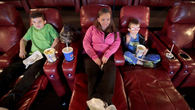 Movie-goers, from left, Ethan, Jennifer and Andrew Wethal settle into their DreamLoungers Thursday at Appleton Marcus Valley Grand Cinema.