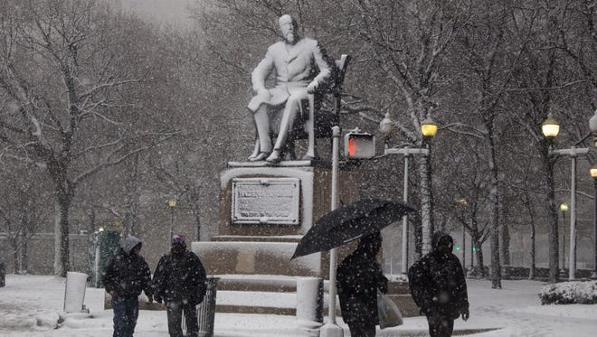 The statue of Hazen S. Pingree in Grand Circus Park is covered with snow as metro Detroiters make their way up a snowy Woodward Avenue Thursday March 1, 2018.