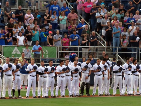 The Pensacola Blue Wahoos gather on the field for the singing of the National Anthem in September 2015 before the start of the third game in their five-game semifinal series against the Biloxi Shuckers in Pensacola.